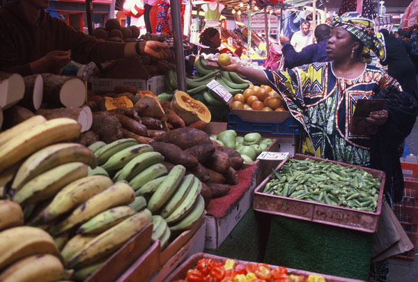 Woman in traditional African dress shopping for fruit in Brixton Market